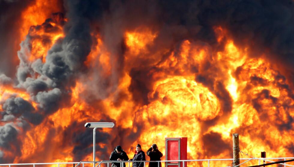 STORE FLAMMER: Tilskuere tar bilder, faretruende nær de enorme flammene som spruter opp av en oljetank i den israelske byen Haifa.Foto: Baz Ratner/Reuters/NTB Scanpix