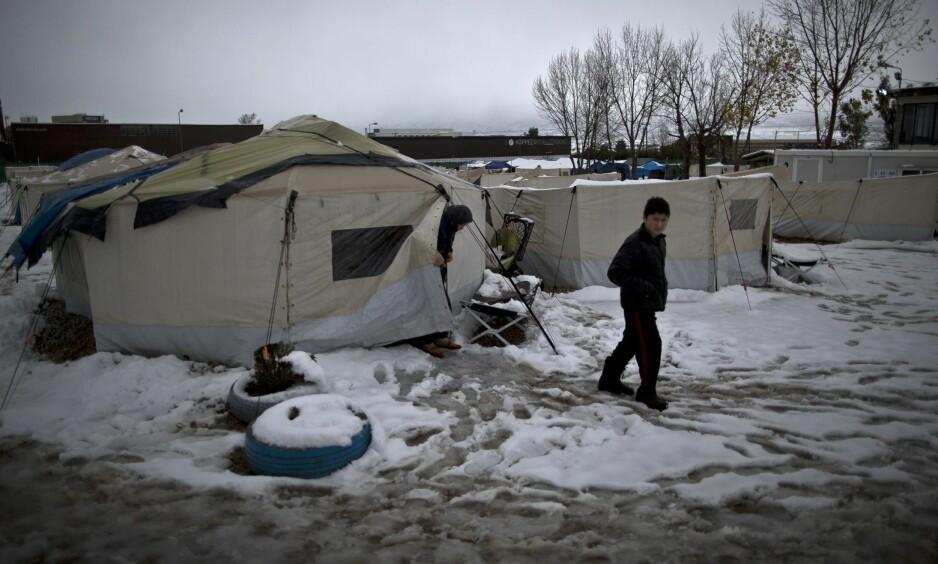 SNØ I HELLAS: Slik så verden ut for en afghansk flyktning i en leir seks mil utenfor Aten i Hellas i forrige uke. Om lag 60 000 flyktninger og migranter er strandet i Hellas etter at de baltiske statene stengte grensene og EU ble enig med Tyrkia om en avtale. Foto: Muhammed Muheisen  / AP / NTB Scanpix