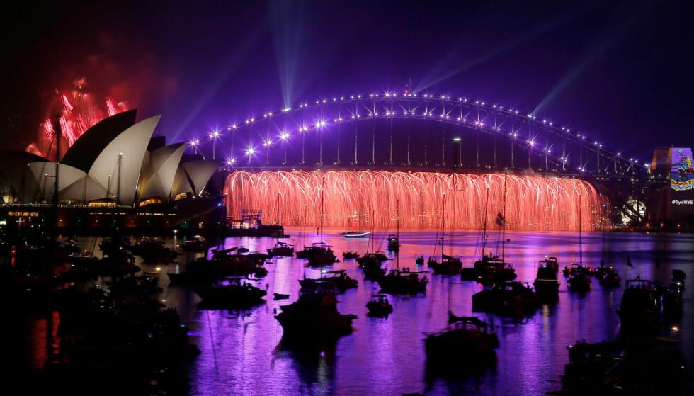 NYTTÅRSAFTEN: På jordas bakside (eller forside, om man vil) er befolkningen godt i gang med å feire det nye året. Himmelen over havna i Sydney ble farget lilla. Foto: NTB Scanpix