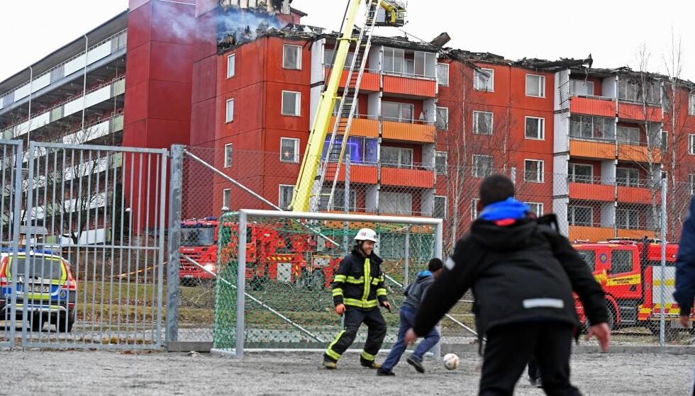PAUSE: Brannmennene tok en pause i slukkingsarbeidet for å spille litt fotball med barna som bor i området etter brannen i svenske Husby. Foto: PER-OLOF SÄNNÅS / Aftonbladet / IBL Bildbyrå / NTB Scanpix