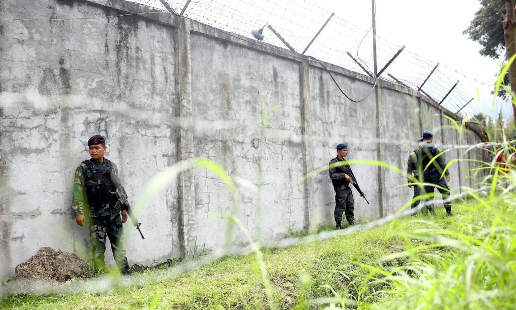 HOLDER VAKT: Væpnede politimenn holder vakt utenfor fengselet, hvor over 100 innsatte rømte etter et angrep i natt. Foto: Althea Ballentes / EPA