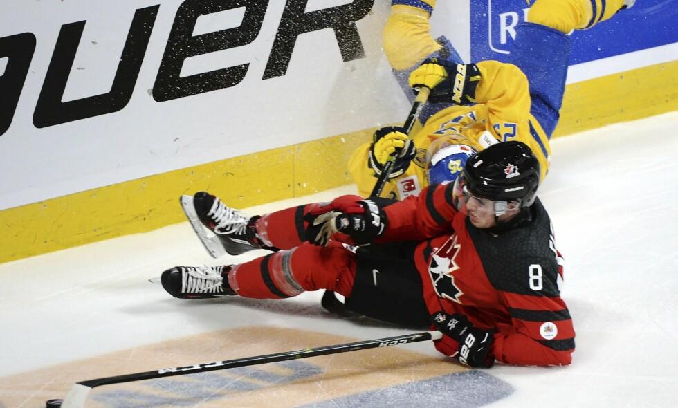 IRRITERTE: Svenske hockeyspillere mener motstanderne fra Canada filmet og falt for lett i semifinalen i junior-VM. Her er Sebastian Ohlsson i duell med Dante Fabbro. Foto: NTB Scanpix/Paul Chiasson/The Canadian Press via AP