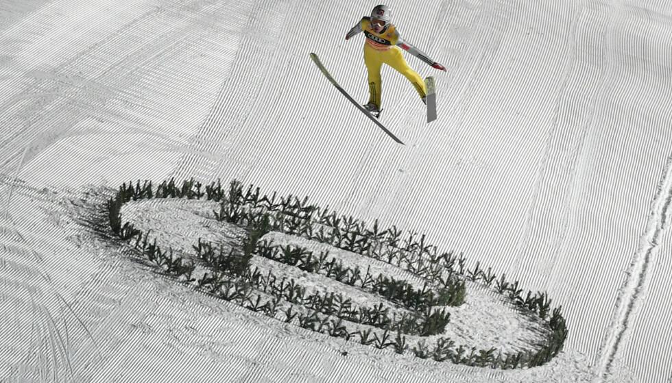 LØS SKI: Bindingen er ødelagt på venstreskia, og Daniel-Andre Tande flyr ukontrollert gjennom lufta. FOTO: AFP/ Barbara Gindl.