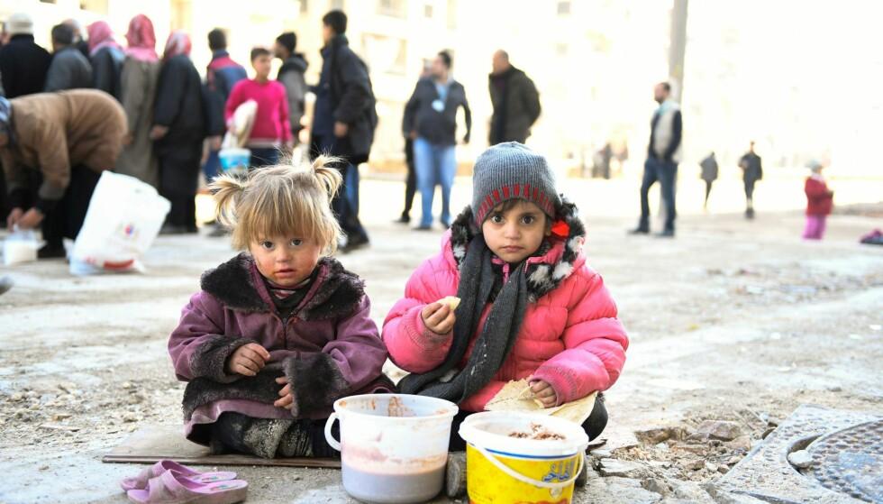 BELEIRET: På dette bildet fra forrige uke spiser disse to jentene i Øst-Aleppo mat som de har fått fra en organisasjon som samarbeider med FN. Foto: Bassam Diab / UNHCR / Reuters / NTB Scanpix