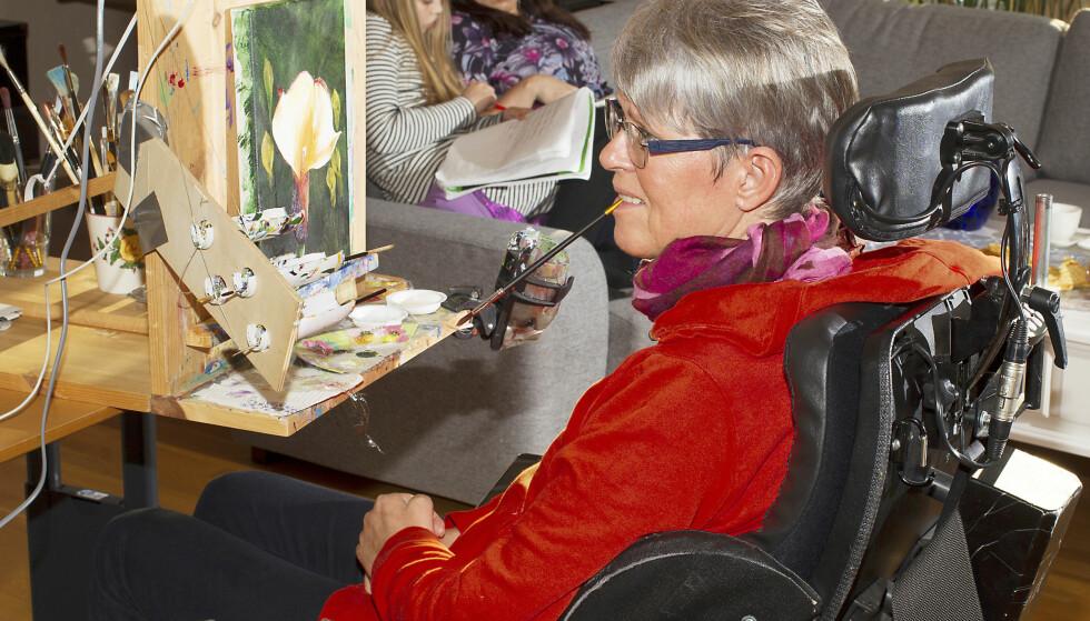 MALER MED MUNNEN: Wenche er glad i å male. Men ettersom hun ikke har armer som fungerer, må hun førepenselen med munnen. Det tar henne rundt 100 timer å gjøre ferdig et maleri. Foto: Svend Aage Madsen og privat