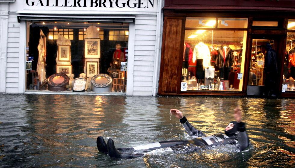 EKSTREMVÆR: Ekstremværet «Inga» førte til stormflo på Bryggen i Bergen og vannet steg fra normalen 1,66 meter til 2,25 meter.  Denne mannen la like godt ut på svømmetur. I dag forventes lignende tilstander. Foto: Oddmund Lunde/Dagbladet