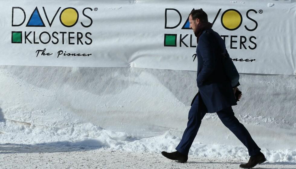 - EN MANN GÅR LANGS ET BANNER I DAVOS: Kronprins Haakon ble ikke kjent igjen av fotografen da han ankom World Economic Forums møte i Davos. Foto: NTB Scanpix