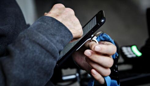 SKRIVER: Kim Andre har laget en egen krok som gjør det mulig for han å ta opp mobilen. Han skriver med knokene, eller med nesa. Foto: Nina Hansen / Dagbladet