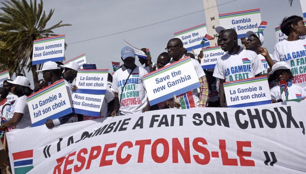 """PROTEST: Demonstranter avbildet under en protest i Dakar 17.desember 2016. På bannerne står det """"Gambia har gjort sitt valg, la oss respektere det"""", og """"Redd demokratiet i Gambia, redd det nye Gambia"""". Foto: AFP PHOTO / SEYLLOU"""