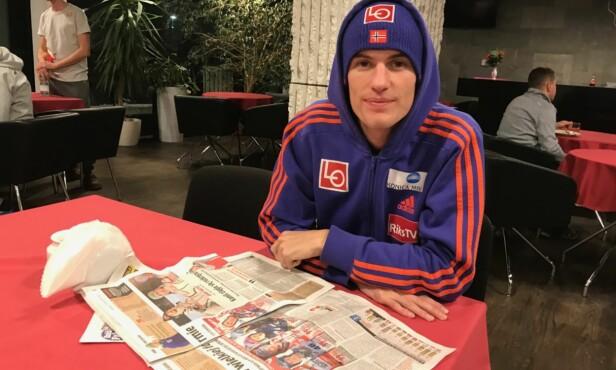<strong>GLEDER SEG:</strong> Daniel-André Tande tar en titt i dagens polske aviser. De er stinne av hoppstoff. FOTO: TORE ULRIK BRATLAND