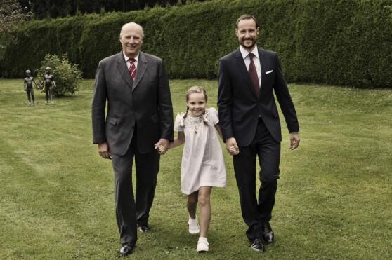 <strong>I 2012:</strong> Prinsesse Ingrid Alexandra hånd i hånd med kong Harald og kronprins Haakon i parken på Skaugum. Foto: Julia Marie Naglestad / Det kongelige hoff / NTB scanpix