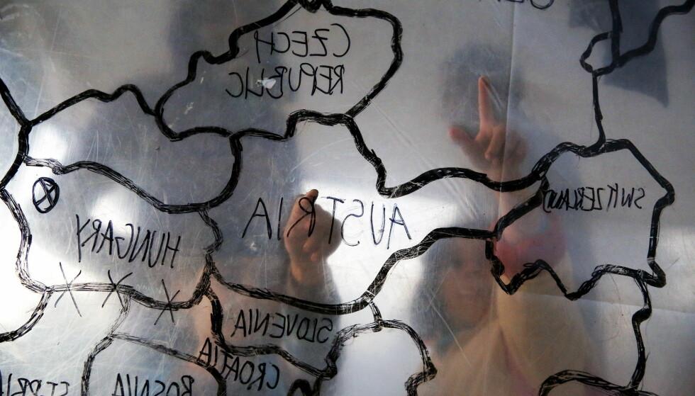 FLERE BARNESLAVER: EU-myndigheter advarer nå mot at flere og flere flyktningbarn ender opp som slaver i Europa. Her peker barn i en flyktningleir i Hellas på ett kart over Europa. Foto: Reuters/Yannis Behrakis/NTB Scanpix