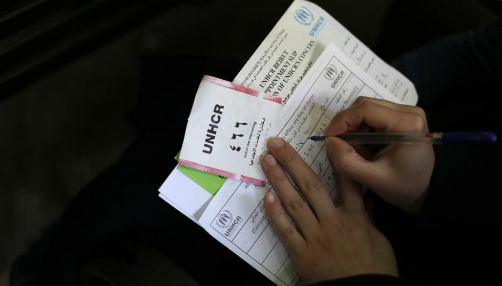 INNREISEFORBUD: En syrisk kvinne fyller ut papirer mens hun venter på å bli registrert hos FNs høykommissær for flyktninger i Libanon. Foto: AP / Hassan Ammar