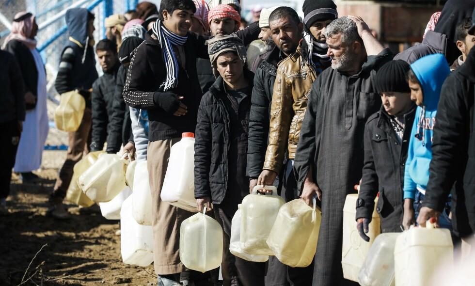 FLYKTNINGER: Flyktninger fra Mosul i kø for fyringsolje i en FN-drevet leir i Syria. Foto: Delil Souleiman / AFP / NTB Scanpix