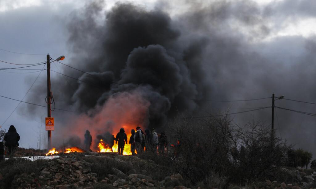 PROTESTER: Rasende demonstranter tente på dekk i forbindelse med at Israelsk politi begynte å kaste ut innbyggere i den ulovlige jødiske bosetningen Amona på Vestbredden forrige uke. Jobben med å demontere husene begynte mandag. Foto: Corinna Kern / NurPhoto / NTB Scanpix