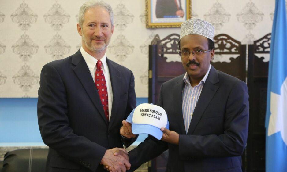 «MAKE SOMALIA GREAT AGAIN:» Her får Somalias nyvalgte president overrakt en noe spesiell caps av USAs ambassadør til Somalia. Capsene Donald Trump gjorde nærmest ikonisk under presidentvalgkampen, har i dette tilfellet blitt justert noe. Foto: USAs ambassade til Somalia