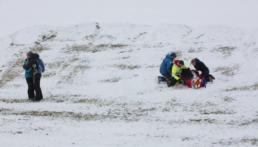 OPERERT: Alexander Sannes Thorsen falt stygt og ble fraktet med helikopter ned til målområdet i båre, og måtte tas hånd om av helsepersonell. Til venstre alpinistens foreldre. Foto: Geir Olsen / NTB scanpix