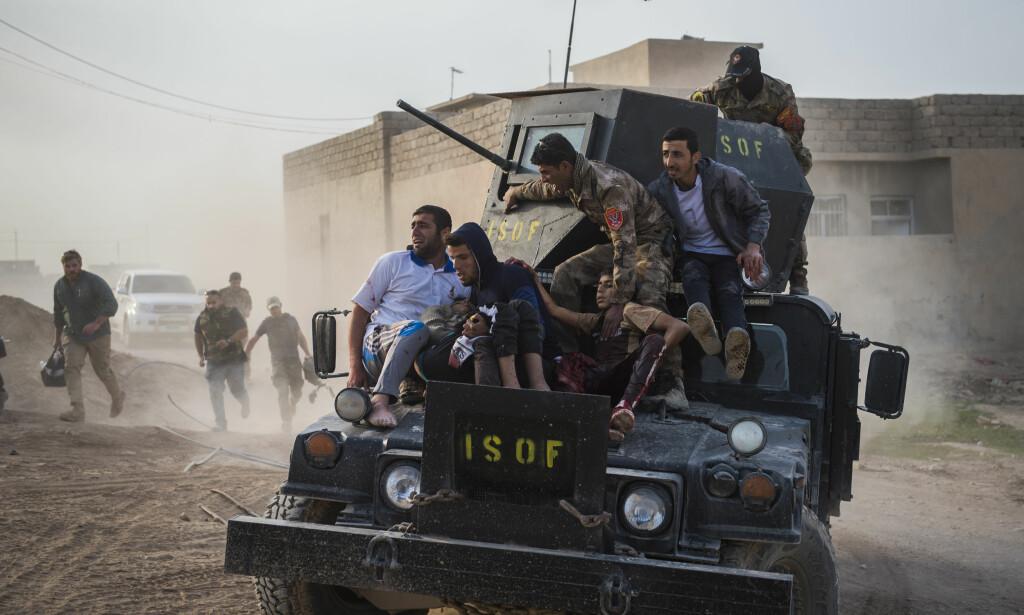 «Kampen om Mosul»: Irakiske soldater og familie evakuerer 12 år gamle Mohammed og 15 år gamle Shafiq, som er blitt ofre for et IS-angrep i nabolaget al Samah. Foto: Odd Reidar Andersen, AFP.