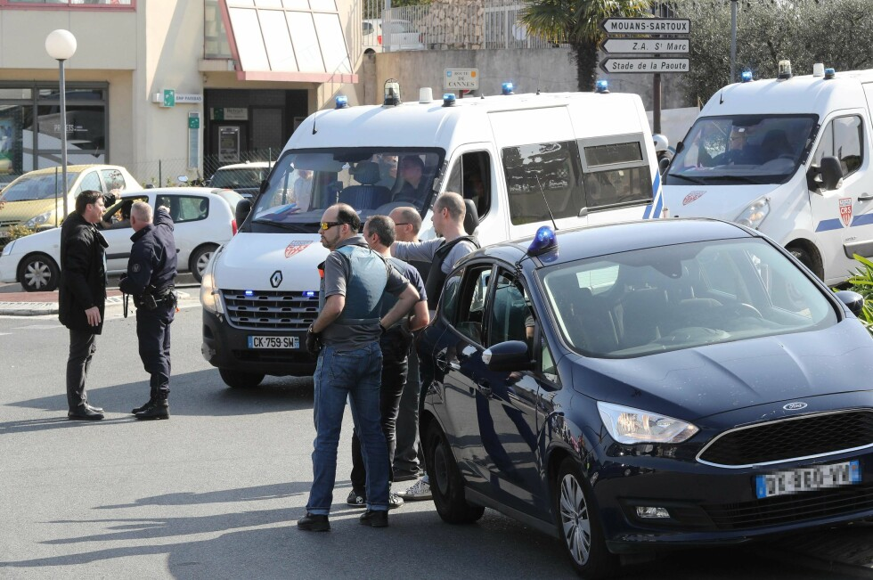 Policemen stand near police vehicles in the southern French town of Grasse, on March 16, 2017 following a shooting in the Tocqueville high school that left two people injured. At least two people were injured in a shooting at a high school in the southern French town of Grasse on March 16, 2017 which saw the head teacher targeted, police and local authorities said. One 17-year-old pupil armed with a rifle, two handguns and two grenades was arrested after the shooting at the Tocqueville high school, a police source told AFP, asking not to be named. / AFP PHOTO / Valery HACHE