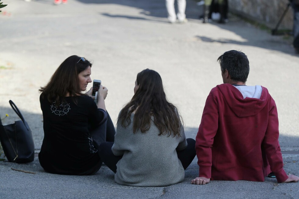 People sit near the Tocqueville high school in the southern French town of Grasse, on March 16, 2017 following a shooting that left two people injured. At least two people were injured in a shooting at a high school in the southern French town of Grasse on March 16, 2017 which saw the head teacher targeted, police and local authorities said. One 17-year-old pupil armed with a rifle, two handguns and two grenades was arrested after the shooting at the Tocqueville high school, a police source told AFP, asking not to be named. / AFP PHOTO / Valery HACHE