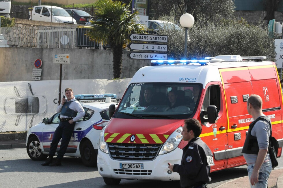 Policemen stand near a police and a firefighter vehicle in the southern French town of Grasse, on March 16, 2017 following a shooting in the Tocqueville high school that left two people injured. At least two people were injured in a shooting at a high school in the southern French town of Grasse on March 16, 2017 which saw the head teacher targeted, police and local authorities said. One 17-year-old pupil armed with a rifle, two handguns and two grenades was arrested after the shooting at the Tocqueville high school, a police source told AFP, asking not to be named. / AFP PHOTO / Valery HACHE