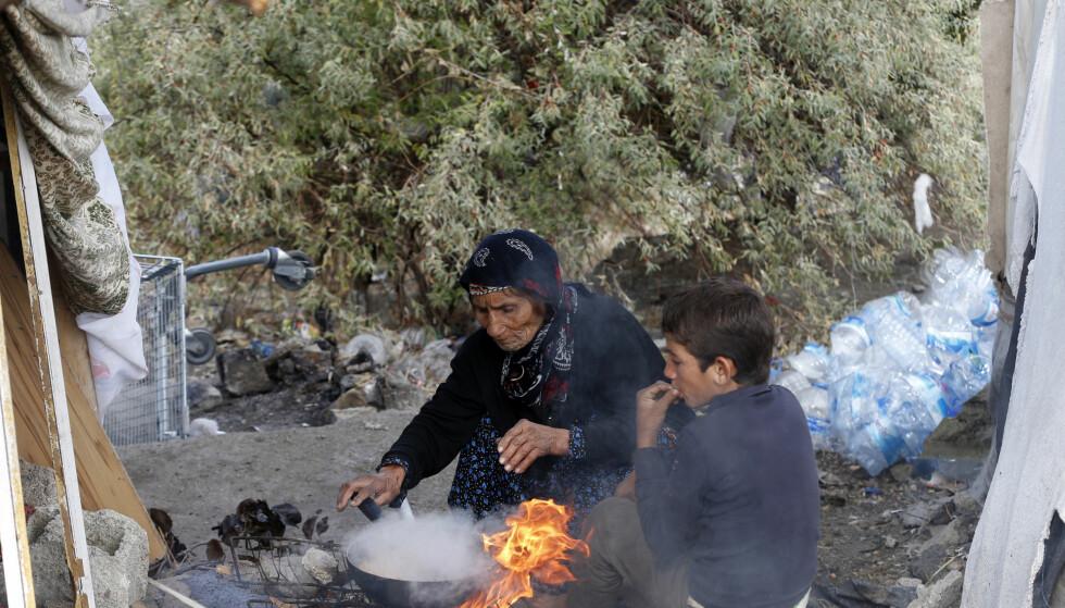 HARDT LIV I TYRKIA: To syriske flyktninger lager mat i foran den provisoriske boligen de har laget i Tyrkias hovedstad Ankara. Hele 2,9 millioner syriske flyktninger bor i Tyrkia, og lever under veldig vanskelige kår. Foto: Umit Bektas / Reuters / Scanpix