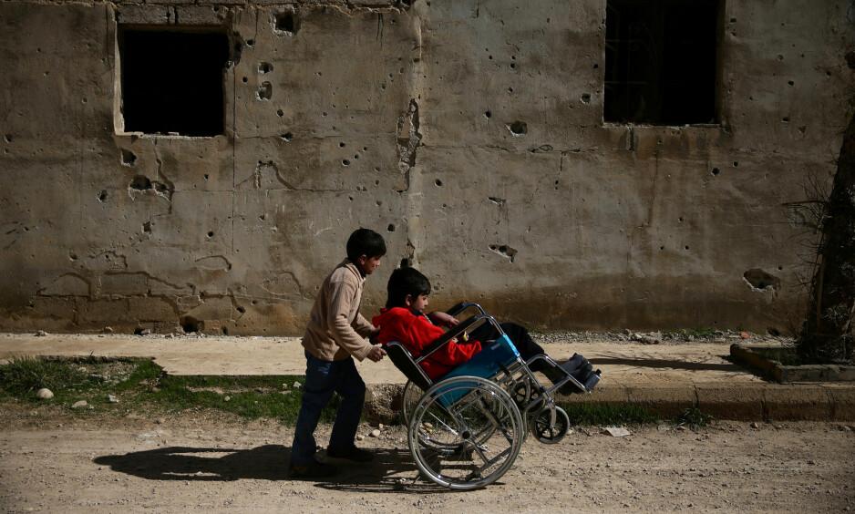 DØD OG LEMLESTELSE: Krigen i Syria har vart i over seks år, og nær en halv million mennesker er drept og et ukjent, men enormt antall millioner syrere har blitt skadd for livet. 14-årige Ziad (t.h) har fått skadet ryggen og må tilbringe livet i rullestol. Her sammen med en hjelpende venn i Douma, en forstad like utenfor Damaskus. Foto: Bassam Khabieh / Reuters / Scanpix