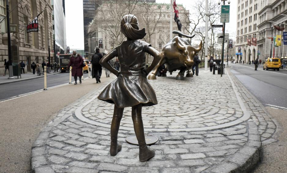 MOTSETNINGER: Den fryktløse jenta er satt opp slik at hun trosser den rasende oksen, og er blitt et symbol på kampen mot mannsdominansen i finansverdenen. Foto: Mark Lennihan / AP / NTB Scanpix