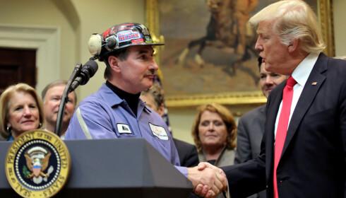 HOLDER KULLØFTET: Kullgruvearbeideren Mike Nelson fikk president Donald Trumps løfte om å fjerne Obamas restriksjoner mot kullgruveindustrien under et møte i Det hvite hus 16. februar. Nå Trump signert løftet. Foto: Carlos Barria, Reuters/NTB Scanpix.