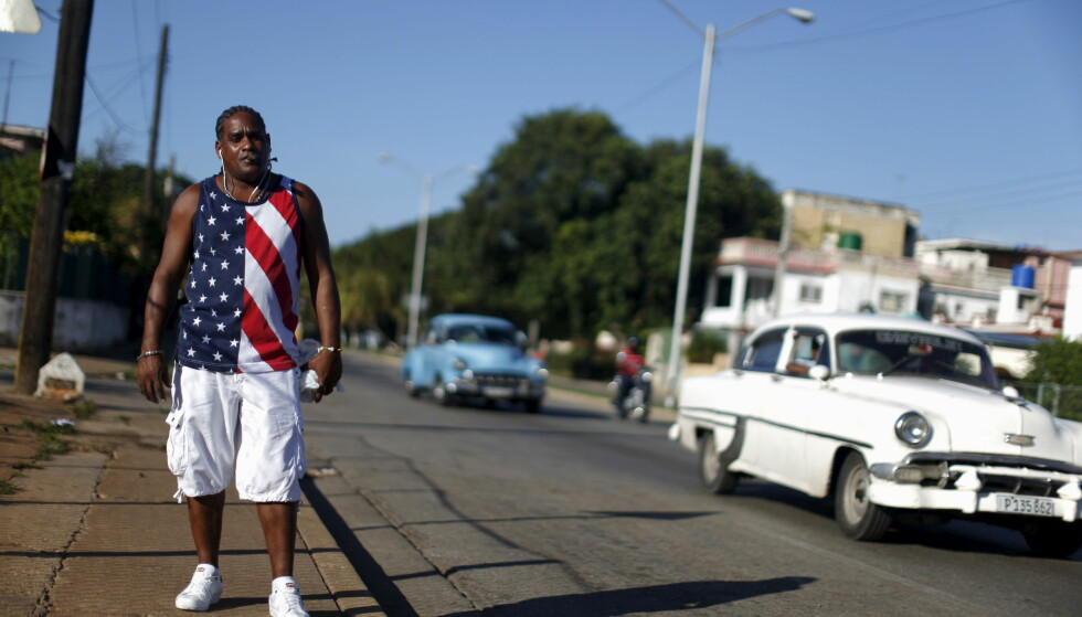 SYMBOLIKK: En kubaner poserer med ei T-skjorte som sender tydelige signaler på gata i Havanna. Barack Obama myket opp relasjonene til Cuba, og nå går det daglige fly til Cuba fra USA. Hva Donald Trump vil gjøre med relasjonen, er det ingen som tør svare på.Foto: Carlos Garcia Rawlins / Reuters / NTB Scanpix