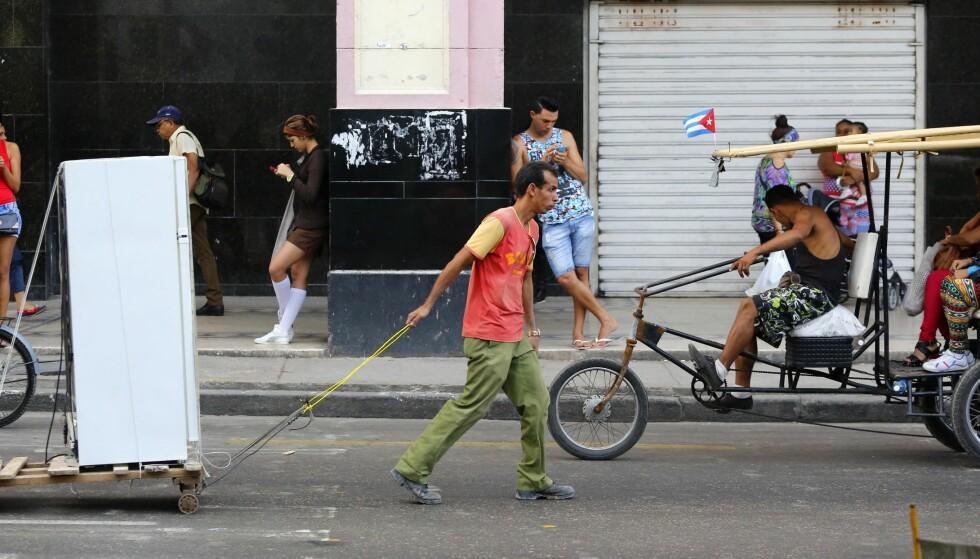 WI-FI-SONER: Der internett før var helt forbudt, er det nå poppet opp wi-fi-soner rundt omkring, spesielt i Havanna. Her står mange og surfer i en slik sone, mens hverdagslivet og turistlivet passerer på gata. Foto: Desmond Boyland / AP / NTB Scanpix