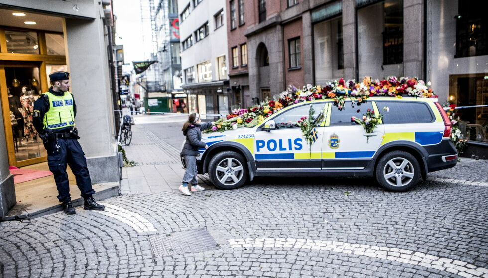 BLOMSTER: Ei jente legger blomster på en politibil i Stockholm sentrum etter lastebilangrepet som fant sted fredag forrige uke. Foto: Christian Roth Christensen / Dagbladet