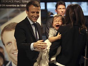 FORFATTER: Emmanuel Macron hilser på en datter under en boksigneringsseanse i Paris. Foto: NTB Scanpix