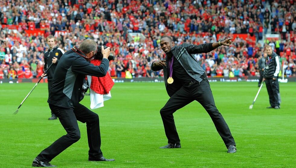 VIL INN PÅ EN ANNEN ARENA: Manchester United-tilhengeren Usain Bolt vil prøve seg som fotballspiller når friidrettskarrieren snart er over. Her er han på Old Trafford før en kamp mellom Manchester United og Fulham i 2012. Foto: AFP /ANDREW YATES/ NTB Scanpix