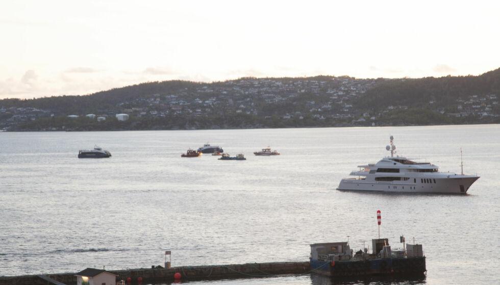 STYRT: Redningsmannskaper i sjøen utenfor Sandviken i Bergen hvor et helikopter styrtet onsdag kveld. Ifølge vitner prøvde helikopteret å lande på denne yachten da det gikk galt. Foto: Tilla Bønes