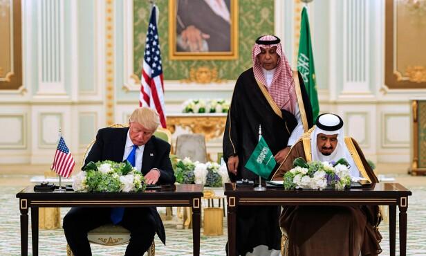 STRATEGISK: Mens skandaleoppslagene om president Donald Trump florerer hjemme i USA, er presidenten selv på statsbesøk i Saudi-Arabia. I kveld signerte han og kong Salman bin Abdulaziz al-Saud en våpenavtale og flere andre avtaler under en seremoni ved det kongelige palasset i Riyadh.  Ifølge Saudi-Arabias utenriksminister har avtalene  en samlet verdi på over 380 milliarder dollar. Foto: AFP/Saudi Royal Palace / Bandar Al-Jaloud