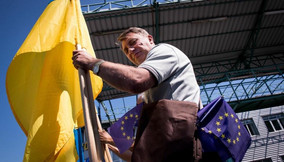 UKRAINA FEIRER: En mann feirer visumfriheten med et ukrainsk flagg og EU-flagg. Foto: AFP / NTB Scanpix