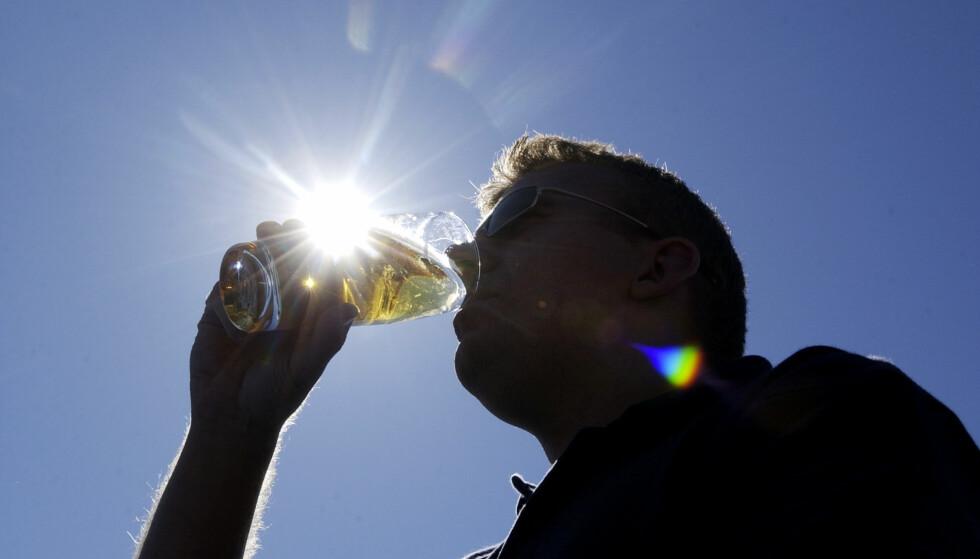 HALVFULL: En mann drikker øl av et havtomt glass. Sola skinner, i det minste. - Noen ganger kan man lure på om det å være optimist er blitt en slags moralsk posisjon - ved at det oppfattes som et godt karaktertrekk å være optimist, skriver artikkelforfatteren. Foto: Thomas Bjørnflaten / SCANPIX