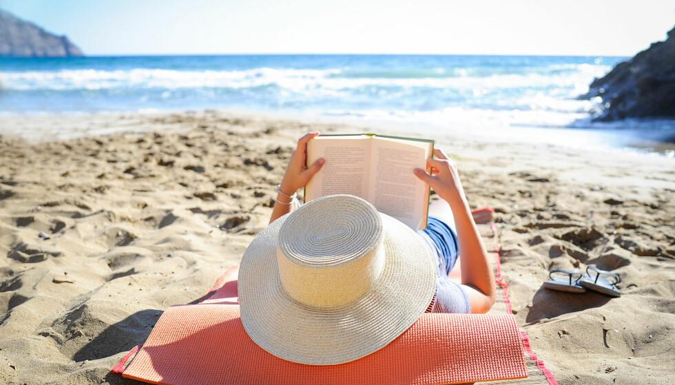 STRANDLEKTYRE: Mange foretrekker lett lektyre på stranda. Dagbladets anmelder har lest og vurdert sju nye underholdningsromaner. Foto: NTB SCANPIX