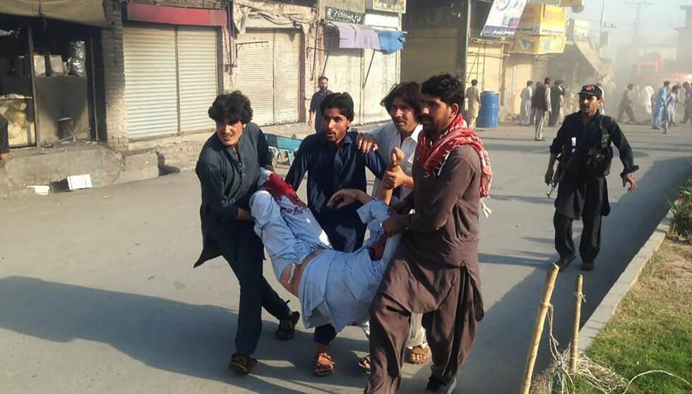 BOMBE PÅ MARKED: En skadd mann blir båret bort etter at en av to bomber eksploderte i byen Parachinar fredag. Foto: AFP/NTB Scanpix.