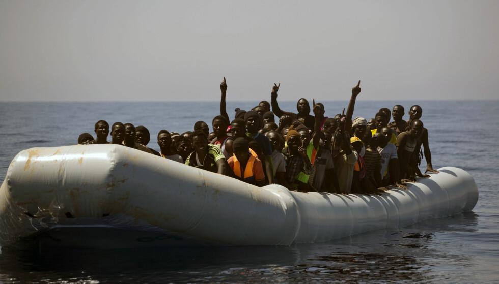 PÅ HAVET: Migranter ber redningsmannskaper om hjelp utenfor kysten av Libya 15. juni i år. Foto: AP Photo/Emilio Morenatti