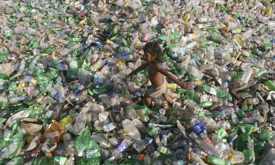 FARLIG AVFALL: Et barn går gjennom en søppelhaug av plastflasker i utkanten av den indiske byen Chandigarh. Hvert sekund kjøpes så mange som 20 000 plastflasker, verden over. Bare en liten brøkdel av disse resirkuleres. Foto: Ajay Verma / Reuters / Scanpix
