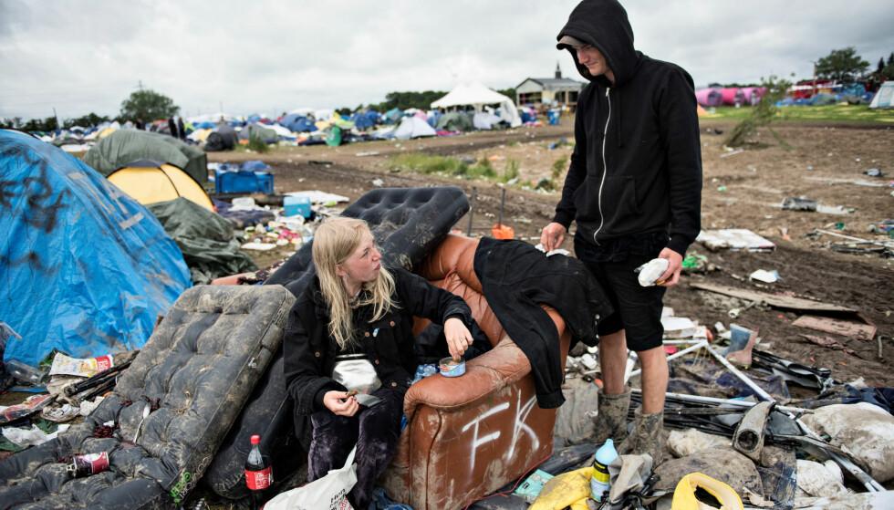 PÅ TIDE Å DRA HJEM: To festivalgjester tar seg en pust i bakken før de forlater Roskildefestivalen 2017. Foto: NTB Scanpix