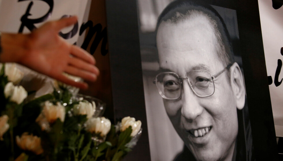I HONG KONG: Blomster legges ned ved et bilde av Liu Xiaobo i Hong Kong, etter at han døde i dag. Foto: REUTERS/Bobby Yip