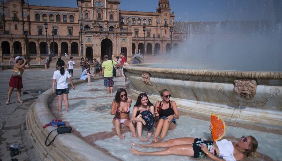 HETEBØLGEN RAMMER HARDT: Turister i Sevilla søker tilfukt i vann for å kjøle seg ned under hetebølgen som rammer Spania. / AFP PHOTO / JORGE GUERRERO