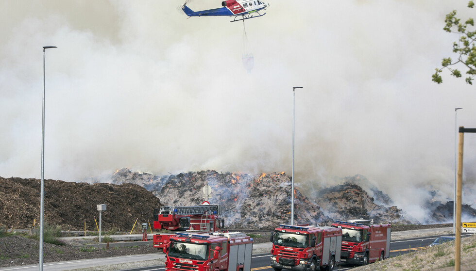 HELIKOPTER: Brannvesenet satt i går inn helikopter i slokkingen av en omfattende ulmebrann i et barkanlegg på Sky i Larvik. Foto: Peder Torp Mathisen / NTB scanpix