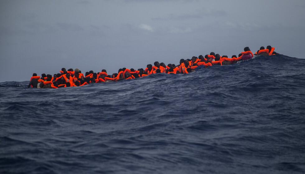 NÆR VED Å DRUKNE: Denne gummibåten var nær ved å gå under da hjelpearbeidere fra det spanske Proactiva Open Arms reddet dem, rundt 20 kilometer utenfor Libyas kyst for to dager siden. Båten var lastet med over 120 personer, inkludert gravide kvinner og barn. Det var også flere døde personer i bunn av båten. Foto: Santi Palacios / Ap / Scanpix