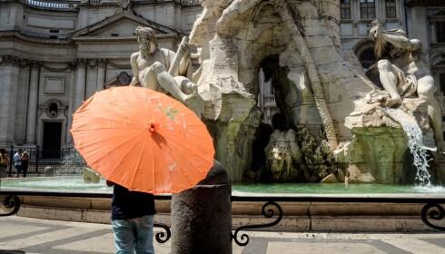 SOLPARAPLY: Mens nordmenn på Vestlandet har opplevd regnrekord, gjemmer turister i Roma seg under paraplyer for å unngå den rekordvarme sola. Foto: Andreas Solaro / Afp / Scanpix