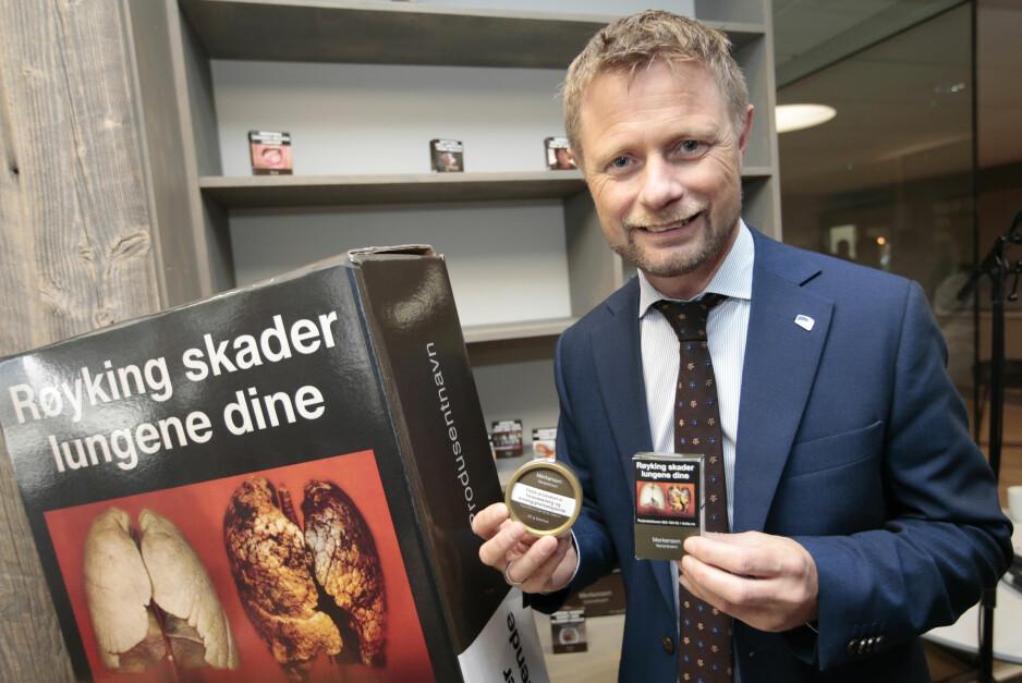 <strong>NYE PAKKER:</strong> Helseminister Bent Høie (H) viser fornøyd fram de nye standardiserte sigarett- og snuseskene. Har vi kommet til et punkt hvor det er greit å sensurere forskning og empiri for å støtte våre politiske holdninger? spør kronikkforfatteren. Foto: Lise Åserud / NTB Scanpix