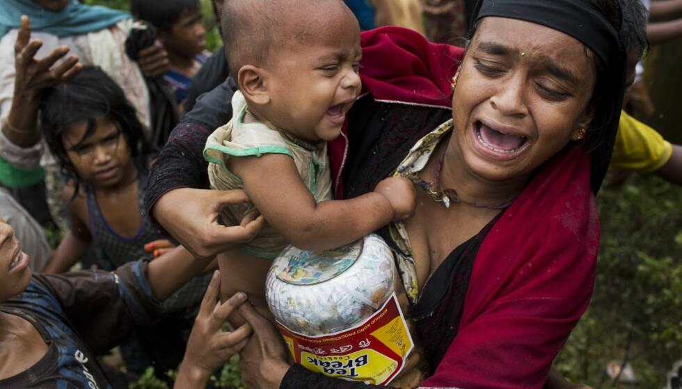 PÅ FLUKT: En rohingya-kvinne og barnet hennes står utslitte i en matkø i Bangladesh og gråter. Titusenvis av rohingyaer forsøker å flykte fra Rakhine-området i Myanmar og til nabolandet Bangladesh. På veien risikerer de å trå på landminer, ifølge Amnesty. Foto: Bernat Armangue / Ap / Scanpix